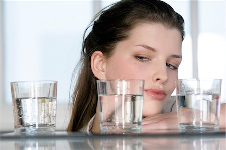Portrait of a young woman looking at 3 glasses of water Stock Photo - Premium Royalty-Free, Code: 6108-05856933