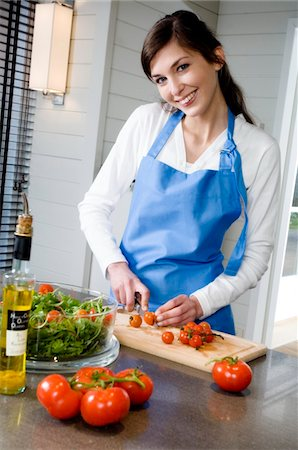 Young smiling woman making a salad, chopping tomatoes Stock Photo - Premium Royalty-Free, Code: 6108-05857052