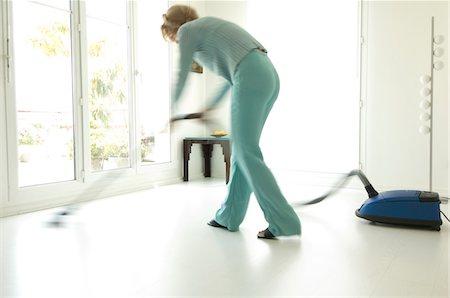 Woman vacuuming in living-room Stock Photo - Premium Royalty-Free, Code: 6108-05857079