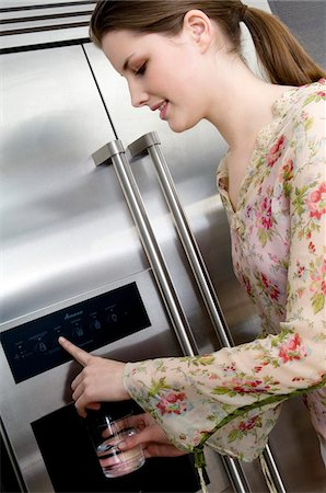 fridge - Young woman pouring water from a refrigerator water dispenser into a glass Stock Photo - Premium Royalty-Free, Code: 6108-05857000