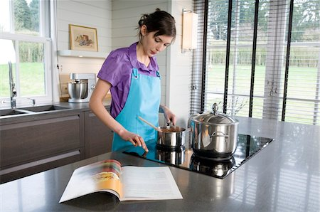 recipe - Young woman cooking, recipe book Stock Photo - Premium Royalty-Free, Code: 6108-05857013