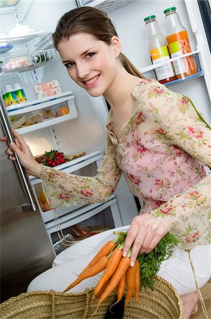 fridge - Young smiling woman filling refrigerator, holding carrots Stock Photo - Premium Royalty-Free, Code: 6108-05857015