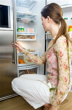 fridge - Woman looking into refrigerator Stock Photo - Premium Royalty-Free, Code: 6108-05857038