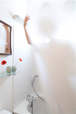 shower - Woman taking a shower, view through shower curtain Stock Photo - Premium Royalty-Free, Code: 6108-05857102