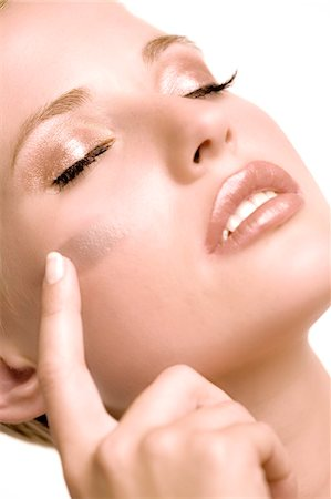 shimmering - Woman putting make-up base on her cheek, shut eyes, indoors (studio) Stock Photo - Premium Royalty-Free, Code: 6108-05857303