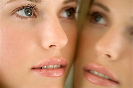 Portrait of a young woman looking at herself in a mirror Stock Photo - Premium Royalty-Free, Code: 6108-05857300
