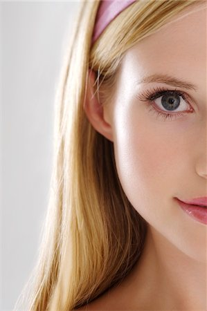 pretty - Young Woman half face with make up, looking at the camera, close-up, indoors (studio) Stock Photo - Premium Royalty-Free, Code: 6108-05857330