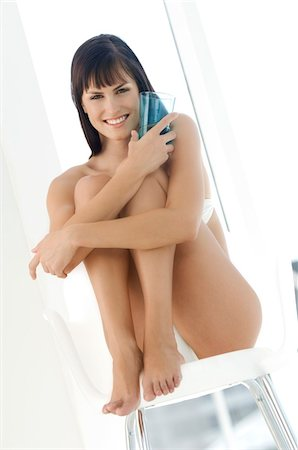 Young smiling woman in underwear sitting on a chair, holding glass of water Stock Photo - Premium Royalty-Free, Code: 6108-05857477