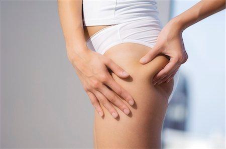 Woman pinching thigh, close-up Stock Photo - Premium Royalty-Free, Code: 6108-05857476