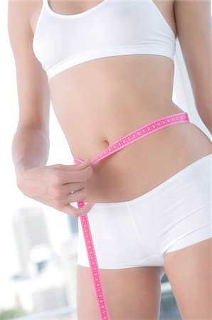 slim - Young woman measuring waist with tape measure Stock Photo - Premium Royalty-Free, Code: 6108-05857494