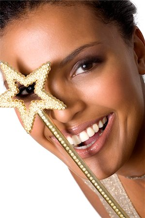 Portrait of a young smiling woman looking through magic wand Stock Photo - Premium Royalty-Free, Code: 6108-05857423