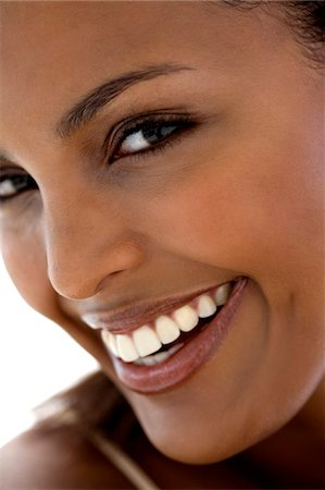 Portrait of a young woman smiling for the camera Stock Photo - Premium Royalty-Free, Code: 6108-05857431