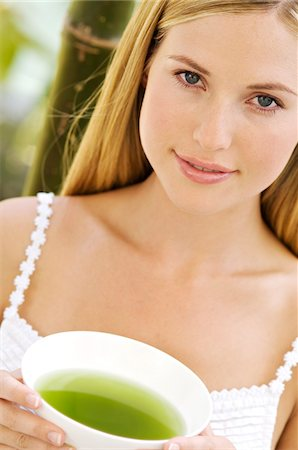 pretty - Portrait of a young woman looking at the camera, holding a green tea cup, outdoors Stock Photo - Premium Royalty-Free, Code: 6108-05857589