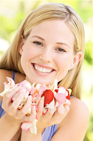 smelling - Portrait of a young  blond woman smiling, holding petals, outdoors Stock Photo - Premium Royalty-Free, Code: 6108-05857524