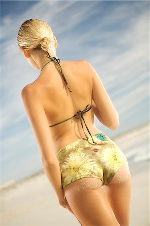 simsearch:400-04002563,k - Young woman in bikini standing on beach, rear view Stock Photo - Premium Royalty-Free, Code: 6108-05857604