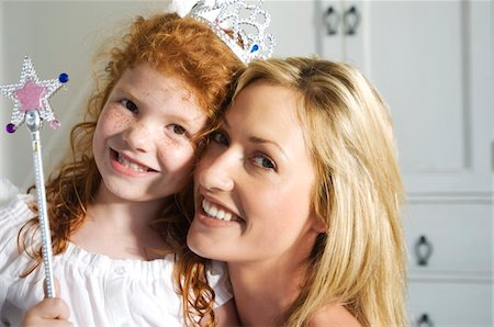 Christmas day, portrait of a mother and daughter smiling, looking at the camera, indoors Stock Photo - Premium Royalty-Free, Code: 6108-05858040