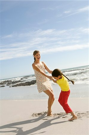 Mother and daughter playing on the beach, outdoors Fotografie stock - Premium Royalty-Free, Codice: 6108-05858067