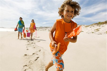 Parents and little boy walking on the beach, outdoors Stock Photo - Premium Royalty-Free, Code: 6108-05858069