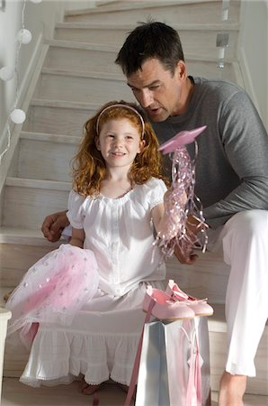 family shoes - Father and daughter with Christmas presents, girl holding a princess costume, indoors Stock Photo - Premium Royalty-Free, Code: 6108-05858017