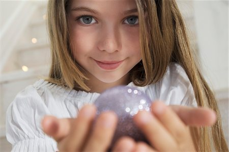 sparkling - Portrait of a little girl posing for the camera, holding a Christmas ball, indoors Stock Photo - Premium Royalty-Free, Code: 6108-05858027