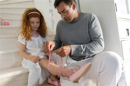 Father and daughter opening Christmas presents, girl holding a princess costume, indoors Stock Photo - Premium Royalty-Free, Code: 6108-05858028