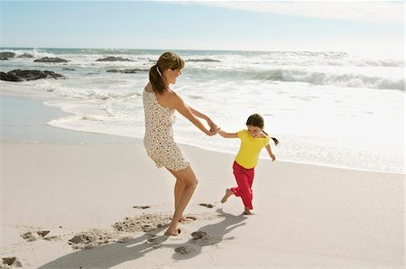 Mother and daughter playing on the beach, outdoors Fotografie stock - Premium Royalty-Free, Codice: 6108-05858140