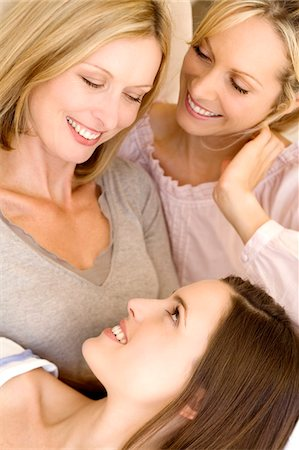 Three smiling women looking at each other, indoors Stock Photo - Premium Royalty-Free, Code: 6108-05858166