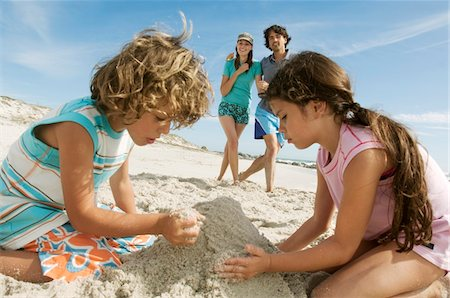 family fun day background - Two children playing on the beach, parents in background, outdoors Stock Photo - Premium Royalty-Free, Code: 6108-05858113