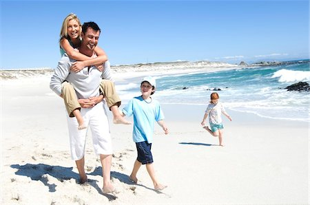 figura - Parents and two children walking on the beach, man carrying woman on his back, outdoors Foto de stock - Sin royalties Premium, Código: 6108-05858111