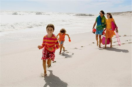 four - Parents and two children walking on the beach, outdoors Stock Photo - Premium Royalty-Free, Code: 6108-05858112