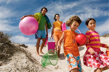 Parents and two children walking on the beach, outdoors Stock Photo - Premium Royalty-Free, Code: 6108-05858115