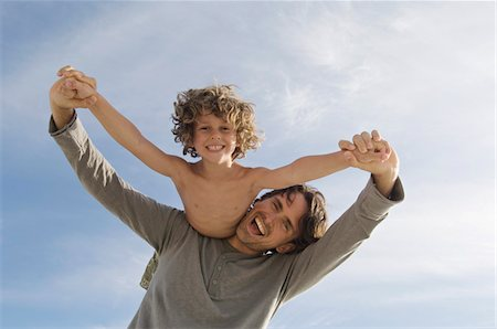 Portrait of a father carrying his son on his back, outdoors Stock Photo - Premium Royalty-Free, Code: 6108-05858127