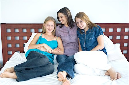 Mother and two teenagers sitting on a bed, indoors Stock Photo - Premium Royalty-Free, Code: 6108-05858272
