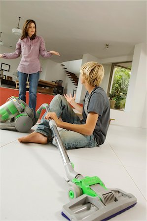Mother and son in living room, vacuum cleaner, indoors Stock Photo - Premium Royalty-Free, Code: 6108-05858274