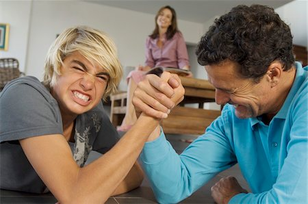 Father and son arm-wrestling indoors, mother in background Stock Photo - Premium Royalty-Free, Code: 6108-05858286