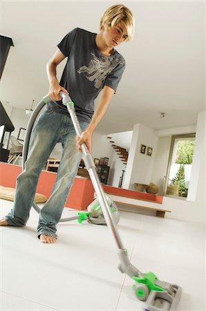 Teenager vacuuming, indoors Stock Photo - Premium Royalty-Free, Code: 6108-05858292