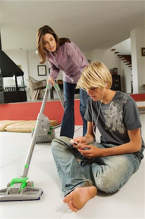 Mother vacuuming and speaking to his son, sitting on floor, indoors Stock Photo - Premium Royalty-Free, Code: 6108-05858295