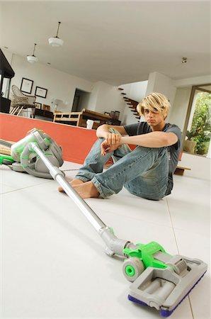 Teenager sitting on floor in living room, vacum cleaner, indoors Stock Photo - Premium Royalty-Free, Code: 6108-05858304