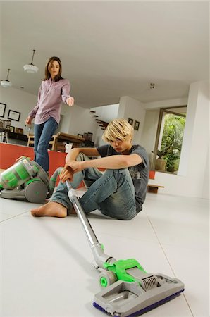 Mother and son in living room, vacuum cleaner, indoors Stock Photo - Premium Royalty-Free, Code: 6108-05858320