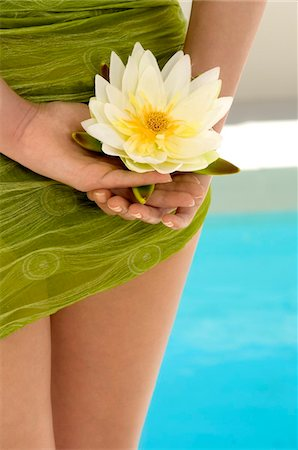 Young woman holding a water lily, pool, outdoors Stock Photo - Premium Royalty-Free, Code: 6108-05858479