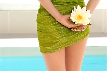 Young woman near a pool, holding a water lily, outdoors Stock Photo - Premium Royalty-Free, Code: 6108-05858496