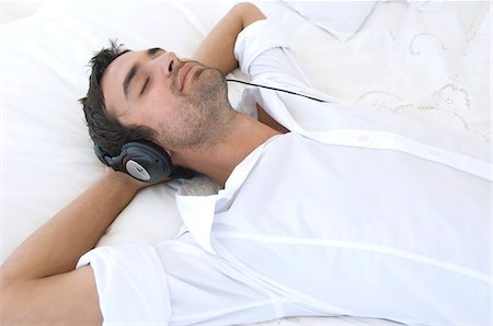 Young man listening to music with headphones Stock Photo - Premium Royalty-Free, Code: 6108-05858583