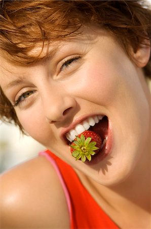 Portrait of a young woman holding strawberry between her teeth Stock Photo - Premium Royalty-Free, Code: 6108-05858535