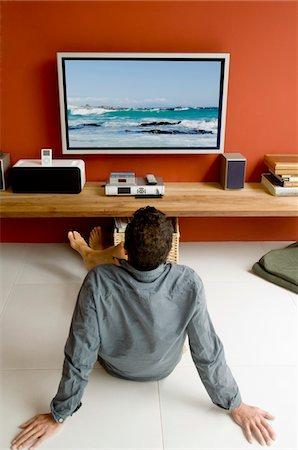 plasma - Man watching TV sitting on floor Stock Photo - Premium Royalty-Free, Code: 6108-05858656
