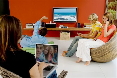 plasma - Family in living room, woman using laptop, man watching TV, 2 teens using mobile phone Stock Photo - Premium Royalty-Free, Code: 6108-05858662