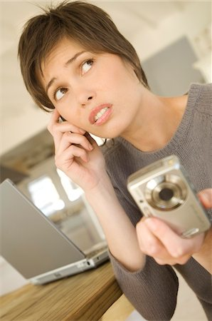 ebusiness - Young woman phoning, holding digital camera Stock Photo - Premium Royalty-Free, Code: 6108-05858688