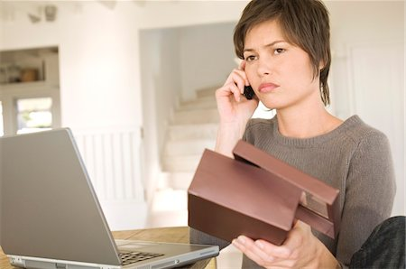 ebusiness - Young woman with laptop, phoning, holding box Stock Photo - Premium Royalty-Free, Code: 6108-05858698