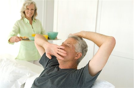 Woman bringing breakfast to man yawning in bed Stock Photo - Premium Royalty-Free, Code: 6108-05858722