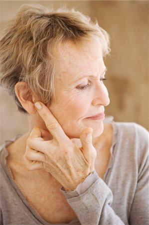 Portrait of senior woman touching her ear Stock Photo - Premium Royalty-Free, Code: 6108-05858854