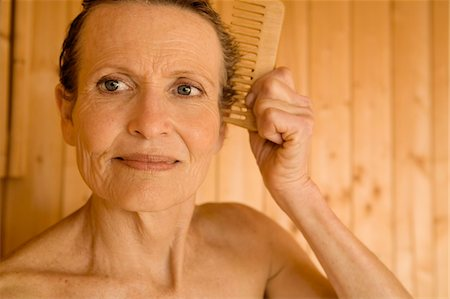 Portrait of senior woman combing her hair Stock Photo - Premium Royalty-Free, Code: 6108-05858879